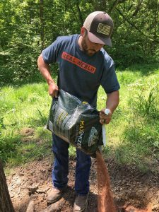 Hunter dumping out custom deer minerals at a mineral site where they are trying to grow big bucks.