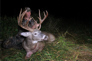 Hunter holding Giant Buck that got big by eating Deer Minerals